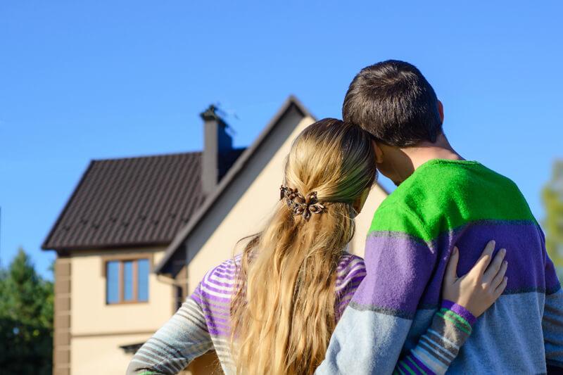 Rückenansicht von Paar vor einem Haus