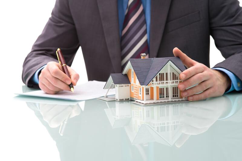 Finanzexperte mit Musterhaus macht Notizen