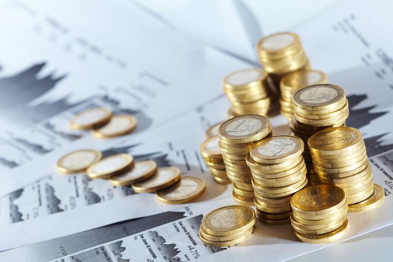 Euro-Münzen gestapelt auf Statistikausdrucken