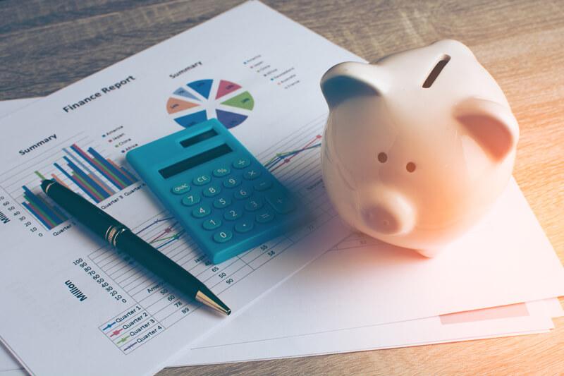Taschenrechner und Sparschwein auf Statistikausdrucken