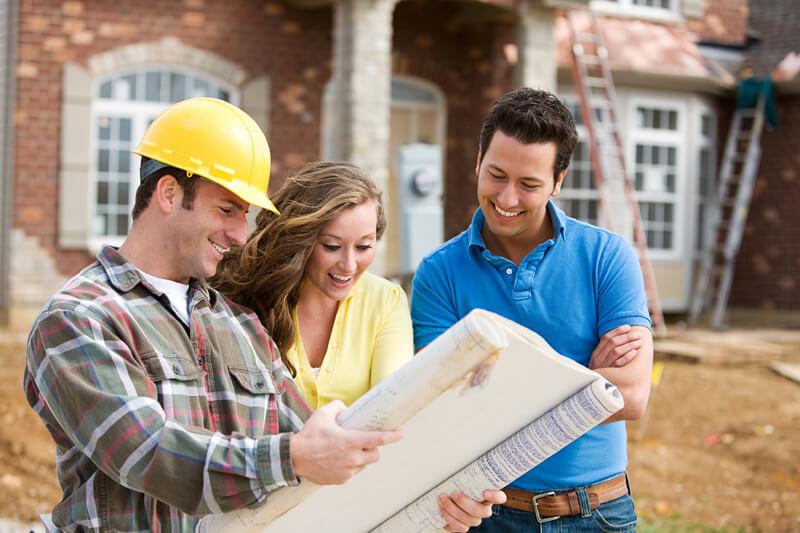 Bauleiter mit jungem Paar vor Neubau