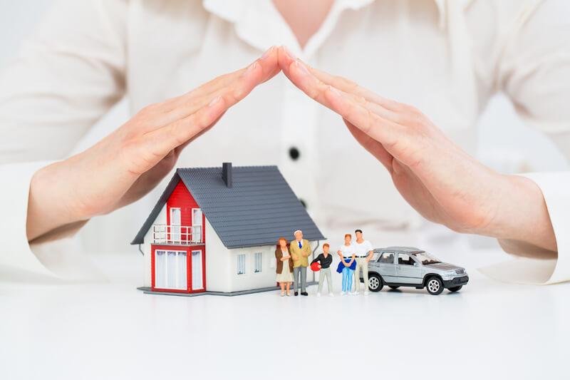 Hände bilden ein Dach über einem Spielzeughaus